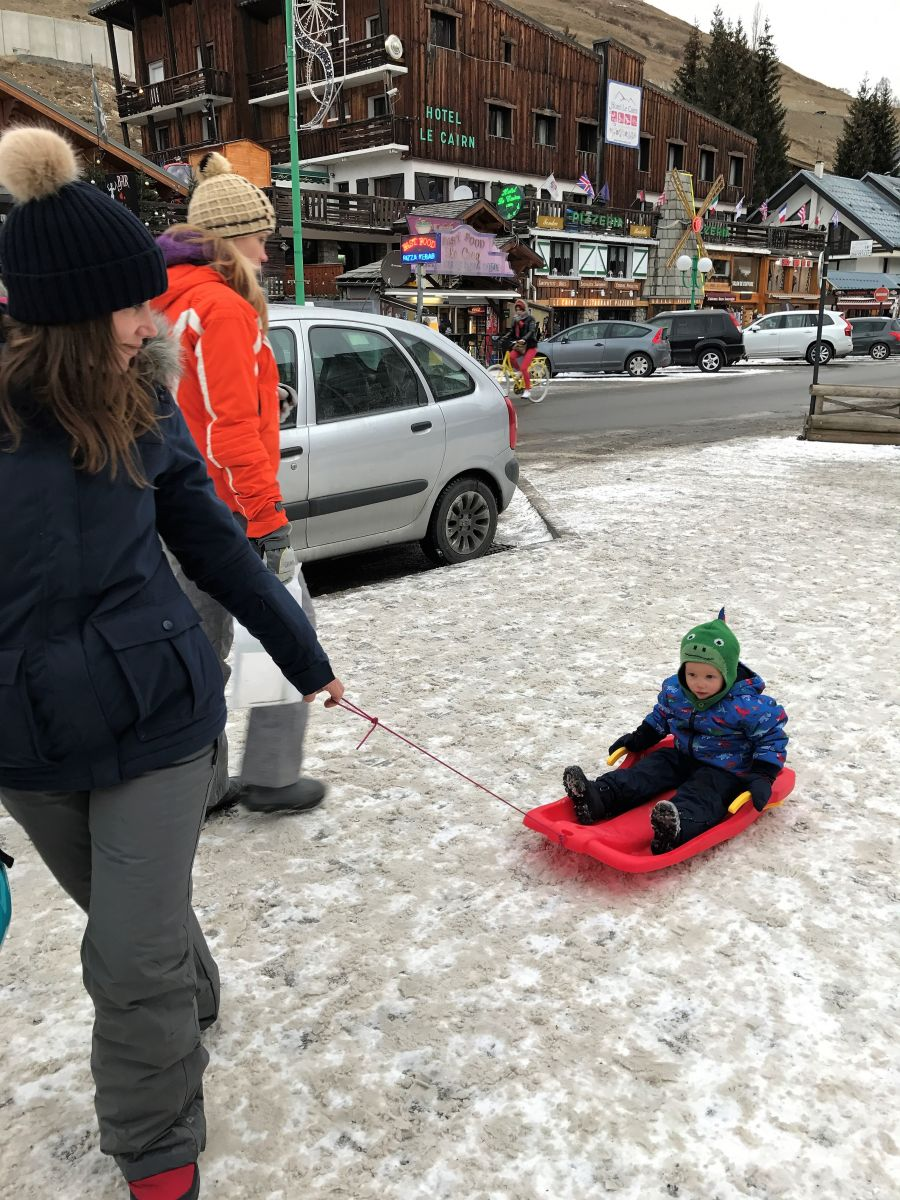 Toddler sitting on a red sledge