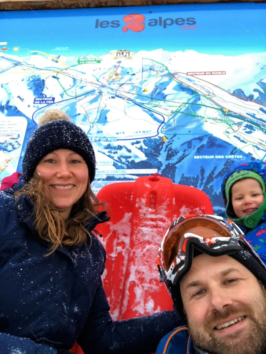 Family standing near Les Deux Alps ski map sign